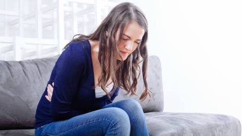 Young Woman Sitting On Sofa Suffering From stomach ache at Home