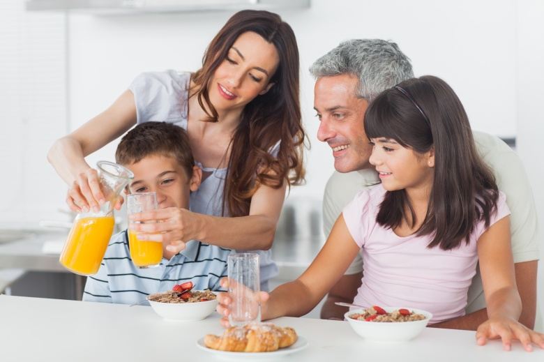 Family eating breakfast in kitchen together at home